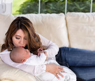 Mom kissing her infant son while resting on white sofa Stock Photo