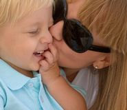 Mom kissing her little son. Mother kissing her cute little blond son Royalty Free Stock Photography