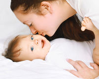 Mom kissing little baby on the bed Royalty Free Stock Image