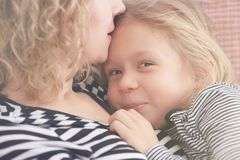 Mom kissing little daughter. Mom kissing young little daughter on the forehead Stock Photos
