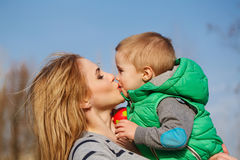 Mom kissing son. Mom kissing her son in autumn park. Family time. Happiness of childhood and motherhood. Outdoor Activities Stock Images