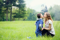Mom kissing son. Young mother plays with her son in a meadow Stock Photo