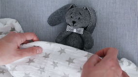 Mom lays a soft toy with a blanke stock video footage