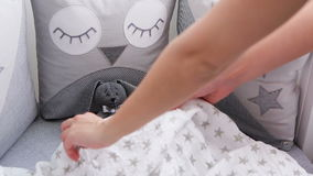 Mom lays a soft toy with a blanke stock footage