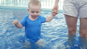 Mom leads a baby`s hand in a children`s pool on the street. Blonde hairless boy less than two years old stock footage