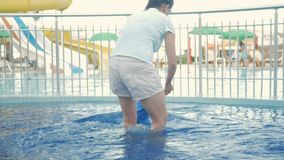 Mom leads a baby`s hand in a children`s pool on the street. Blonde hairless boy less than two years old stock video footage