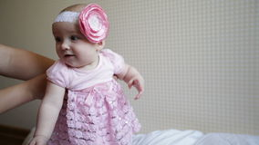 Mom learns to walk a little baby girl in a pink dress stock video footage