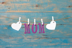 MOM letters. Mothers day message with hearts hanging with clothespins over blue wooden board Stock Photo