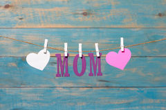 MOM letters. Mothers day message with hearts hanging with clothespins over blue wooden board Stock Images