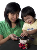 Mom And Litter Girl. Mom and little girl save money in piggy bank Stock Images