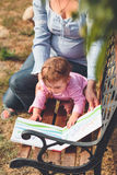 Mom with little baby watching a book with pictures Stock Photo