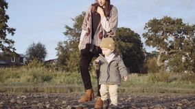 Mom with a little boy walks on the beach stock video footage