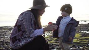 Mom with a little boy walks on the beach stock footage