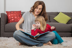 Mom and little child reading a tale book at home Stock Photography