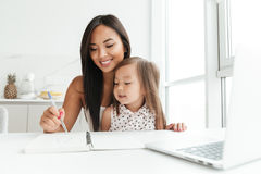 Mom with little cute asian girl using laptop writing notes. Image of amazing young mom sitting at the table with little cute asian girl at home indoors using Royalty Free Stock Photography