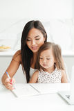 Mom with little cute asian girl using laptop writing notes. Image of amazing young mom sitting at the table with little cute asian girl at home indoors using Royalty Free Stock Image