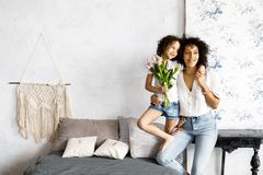 Mom and little cute curly girl spend time together, hugging and kissing each other.  stock images