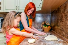 Mom and little cute girl in orange aprons, smiling and making homemade pizza, roll the dough at home in kitchen. Concept happy royalty free stock images
