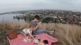 A family of two people, mom and a child on a picnic during the weekend. Mom and a little daughter arranged a picnic on a hill near the city and a pond. Young stock video