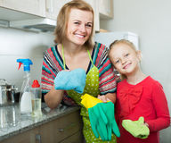 Mom and little daughter cleaning at kitchen Royalty Free Stock Photo