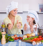 Mom and little daughter cooking vegeterian dish indoors Royalty Free Stock Image