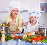 Mom and little daughter cooking vegeterian dish indoors Royalty Free Stock Photos