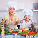 Mom and little daughter cooking vegeterian dish indoors. Happy russian mom and little daughter cooking vegeterian dish indoors Royalty Free Stock Image
