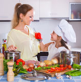 Mom and little daughter cooking vegeterian dish indoors Royalty Free Stock Images