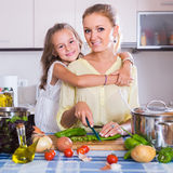 Mom and little daughter cooking vegeterian dish indoors Royalty Free Stock Photography