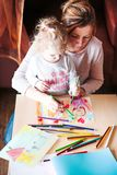 Mom with little daughter drawing a colorful pictures using penci. Mom with little daughter drawing a colorful pictures of family using pencil crayons sitting at Royalty Free Stock Image