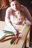 Mom with little daughter drawing a colorful pictures using penci. Mom with little daughter drawing a colorful pictures of house and playing children using pencil Royalty Free Stock Image