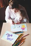 Mom with little daughter drawing a colorful pictures using penci. Mom with little daughter drawing a colorful pictures of house and playing children using pencil Stock Image