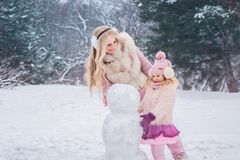 Mom and little daughter dressed in pink clothes have fun and make a snowman in a snowy park stock photo
