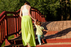 Mom and little daughter go across bridge in park royalty free stock photography