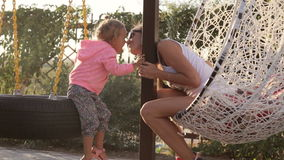 Mom and little daughter having fun on the swing stock video footage