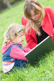Mom and little daughter with laptop outdoor Royalty Free Stock Images