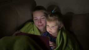 Mom with a little daughter lying on the bed under the blanket watching the screen of the electronic tablet