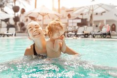 Mom and little daughter are played in the open swimming pool. Family with one child on vacation in warm countries. Positive people stock photos