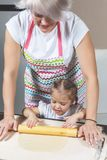 Mom and little daughter roll out the dough for making cookies stock photography