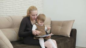 Mom with little daughter sitting on the couch holding a tablet. Mom with a little daughter sitting on the couch holding a tablet and showing her daughter stock video