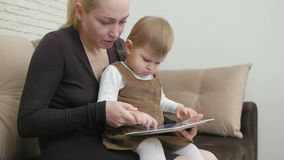 Mom with little daughter sitting on the couch holding a tablet. Mom with a little daughter sitting on the couch holding a tablet and showing her daughter stock footage