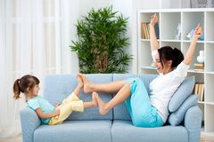 Mom and little daughter are sitting on the sofa, play and having fun. Happy family and parenthood. Leisure with children.  royalty free stock images