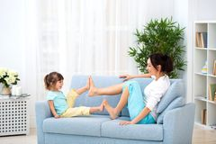 Mom and little daughter are sitting on the sofa, play and having fun. Happy family and parenthood. Leisure with children.  stock image