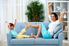 Mom and little daughter are sitting on the sofa, play and having fun. Happy family and parenthood. Leisure with children.  royalty free stock photo