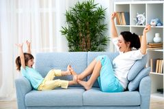 Mom and little daughter are sitting on the sofa, play and having fun. Happy family and parenthood. Leisure with children royalty free stock photography