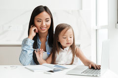 Mom with little daughter using laptop computer. Image of amazing young mom sitting at the table with little cute asian girl at home indoors using laptop computer Royalty Free Stock Photo