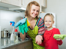 Mom and little girl cleaning at kitchen Stock Photography