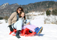 Mom and little girl in the mountain on sledge Stock Photography
