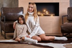 Mom with little girl relaxing on floor near a cozy sofa, Christmas lights in the fireplace. Mom with little girl in white sweaters relaxing on floor near a cozy royalty free stock photography