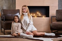 Mom with little girl relaxing on floor near a cozy sofa, Christmas lights in the fireplace. Mom with little girl in white sweaters relaxing on floor near a cozy royalty free stock photos